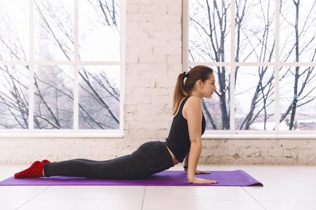 Schöne junge frau, die yoga in der haltung von urdhva-mukha shvanasana im yogastudio auf dem boden nahe dem fenster tut. Premium Fotos