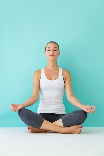 Schöne junge frau, die yoga zu hause tut. Premium Fotos