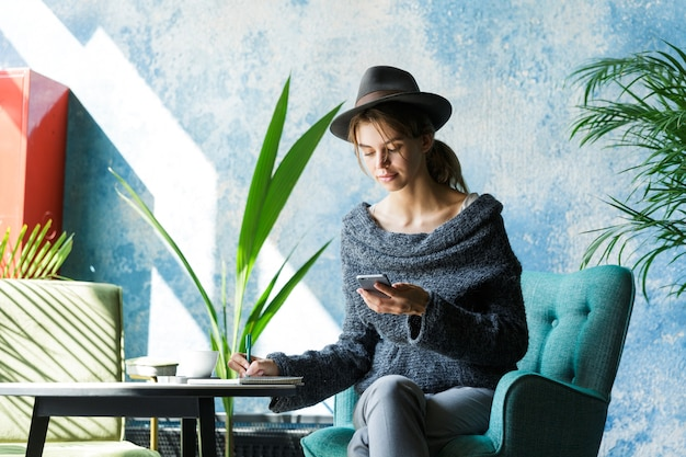 Schöne junge frau gekleidet in pullover und hut, die im stuhl am kaffeetisch sitzen, mit handy, notizen machend, stilvolles interieur Premium Fotos