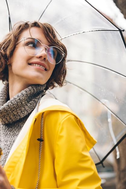 Schöne junge frau, gekleidet in regenmantel Kostenlose Fotos