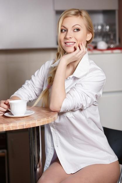 Schöne junge frau hält eine tasse kaffee auf küche Kostenlose Fotos