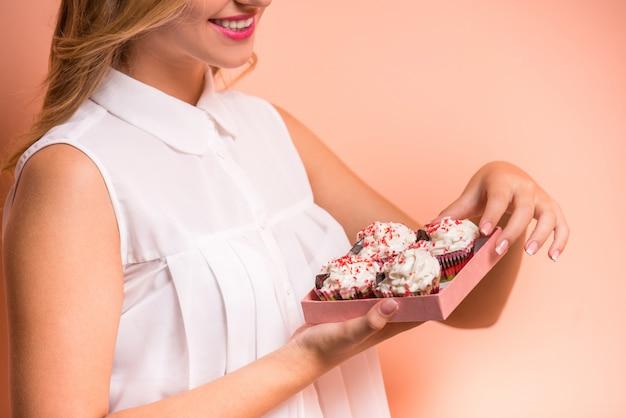 Schöne junge frau hält einen kasten mit kuchen. Premium Fotos