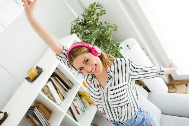 Schöne junge frau hört musik zu hause. Kostenlose Fotos