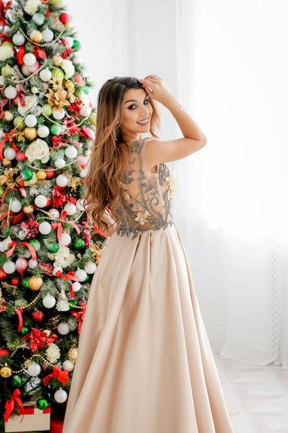 Schöne junge frau im abendkleid nahe weihnachtsbaum. fröhliche weihnachten Premium Fotos