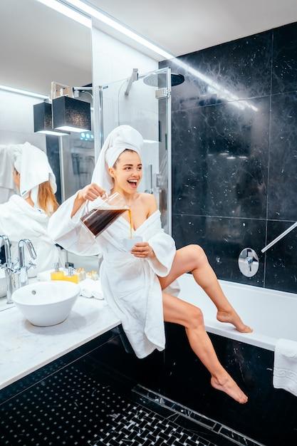 Schöne junge frau im bademantel und im tuch auf ihrem kopf, der auf einer badewanne sitzt Kostenlose Fotos