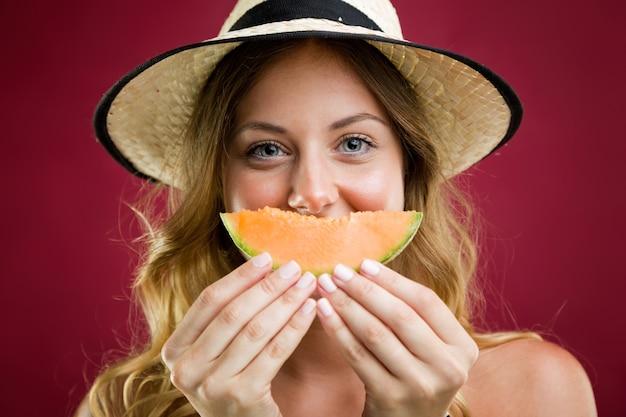 Schöne junge frau im bikini essen melone. isoliert auf rot. Kostenlose Fotos