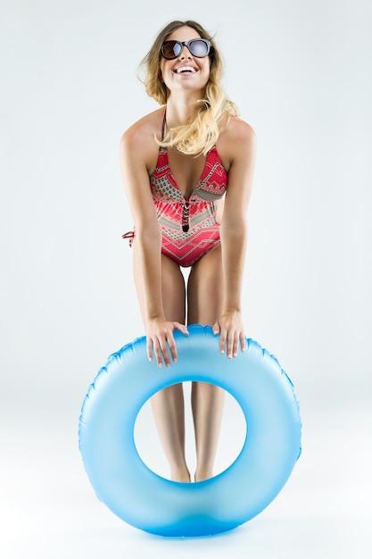 Schöne junge frau im bikini spielen mit schwimmer. isoliert auf weiß. Kostenlose Fotos