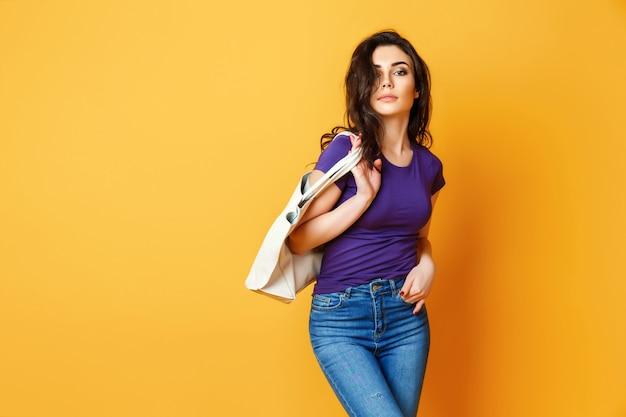 Schöne junge frau im purpurroten hemd, blue jeans, die mit tasche auf gelbem hintergrund aufwerfen Premium Fotos