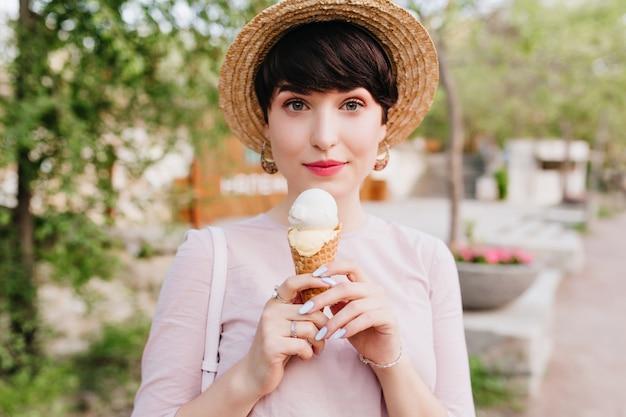 Schöne junge frau im vintage-outfit mit eleganter maniküre, die auf der straße geht und vanilleeis mit vergnügen isst Kostenlose Fotos