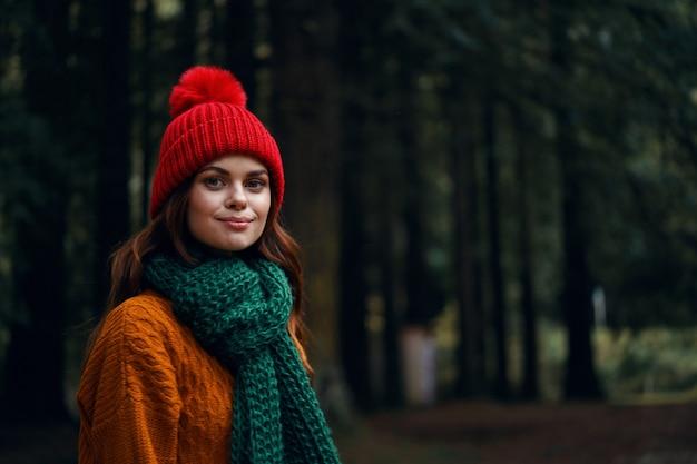 Schöne junge frau im wald in hellen kleidern, einem roten hut, einem orangefarbenen pullover, in einem grünen schal reist, wandert in der natur im wald Premium Fotos