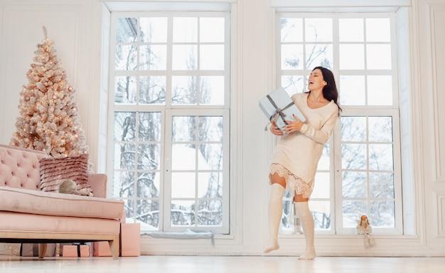 Schöne junge frau im weißen kleid, das mit geschenkbox aufwirft Kostenlose Fotos