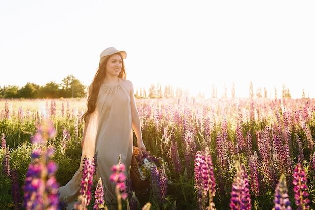 Schöne junge frau im weißen kleid und im strohhut, die in blumenfeld gehen Kostenlose Fotos