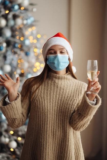 Schöne junge frau in der schutzmaske mit glas champagner zu hause. Kostenlose Fotos