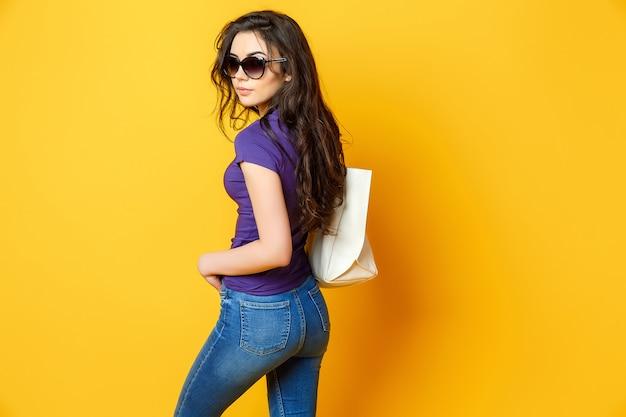 Schöne junge frau in der sonnenbrille, purpurrotes hemd, blue jeans, die mit tasche auf gelbem hintergrund aufwerfen Premium Fotos