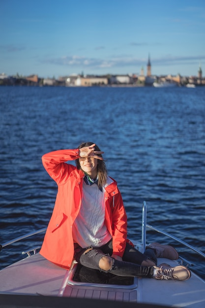 Schöne junge frau in einem roten regenmantel reitet eine private yacht. stockholm, schweden Kostenlose Fotos