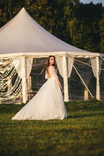 Schöne junge frau in einem weißen hochzeitskleid und in schwarzen stiefeln bei sonnenuntergang. Premium Fotos