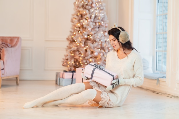 Schöne junge frau in einem weißen kleid mit geschenken in ihren händen Kostenlose Fotos