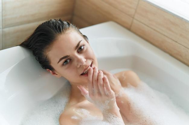Schöne junge frau in ihrer schönen schneeweißen badewanne ruht und entspannt, schöne beweise, badewanne mit schaum Premium Fotos