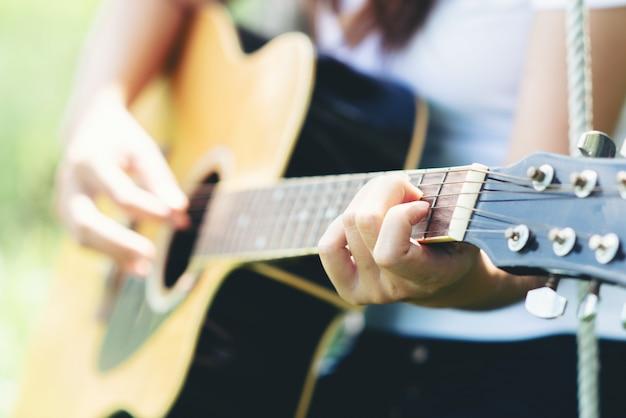 Schöne junge frau mit akustikgitarre an der natur Kostenlose Fotos