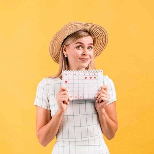 Schöne junge frau mit dem hut, der ovulationskalender zeigt Kostenlose Fotos
