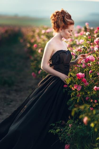 Schöne junge frau mit dem langen lockigen haar, das nahe rosen in einem garten aufwirft Premium Fotos
