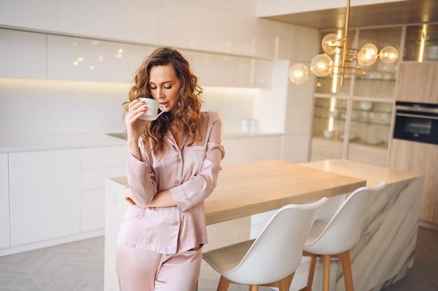 Schöne junge frau mit dem lockigen haar, das kaffee am wochenendmorgen im kuscheligen rosa pyjama trinkt. dame im modernen interieur der weißen küche des skandinavischen stils. Premium Fotos