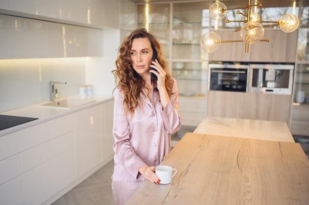 Schöne junge frau mit dem lockigen haar, das kaffee zu hause am faulen wochenendmorgen im gemütlichen rosa pyjama trinkt. Premium Fotos