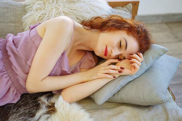 Schöne junge frau mit dem roten haar, das auf der couch liegt. Premium Fotos