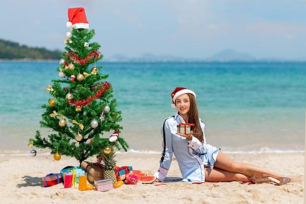 Schöne junge frau mit einem geschenk in ihrer hand feiert weihnachten und neujahr am strand in einer weihnachtsmütze. Premium Fotos