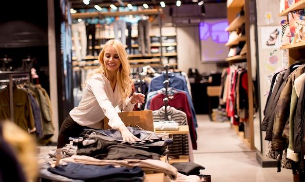 Schöne junge frau mit einkaufstaschen, die am bekleidungsgeschäft stehen Premium Fotos