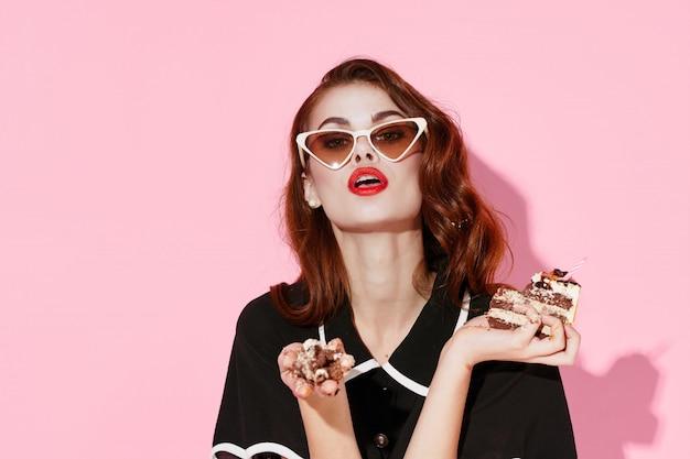 Schöne junge frau mit essen in ihren händen, eine frau, die im studio isst, farbhintergrund, keine diäten Premium Fotos