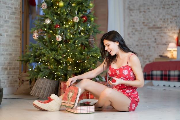Schöne junge frau mit geschenken auf dem weihnachtsbaum Kostenlose Fotos