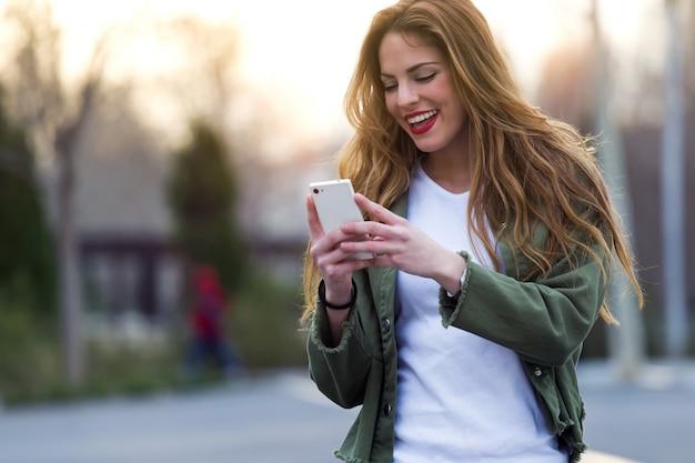 Schöne junge frau mit ihrem handy auf der straße. Kostenlose Fotos