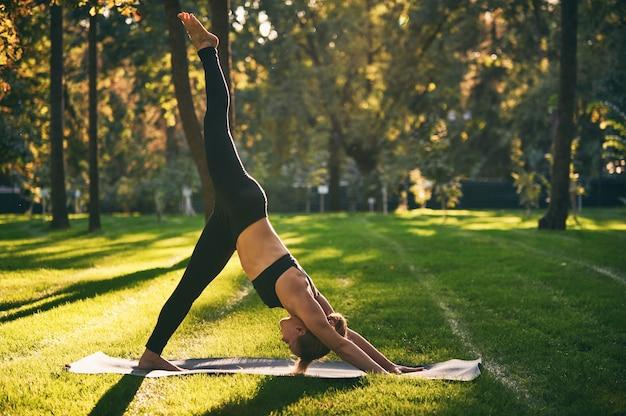 Schöne junge frau praktiziert yoga asana eka pada adho mukha shvanasana - ein bein nach unten hund pose im park Premium Fotos