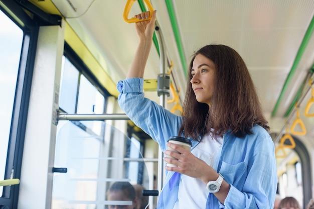 Schöne junge frau trinkt köstlichen kaffee im stadtbus oder in der straßenbahn. konzept des öffentlichen verkehrs. Premium Fotos