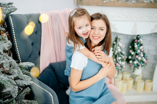 Schöne junge frau und ihre reizend kleine tochter umarmen im gleichen ausstattungslächeln. weihnachtsfeiertage Premium Fotos