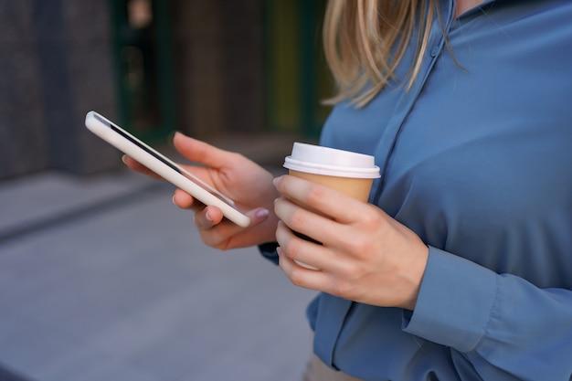 Schöne junge frau verwendet eine app in ihrem smartphone-gerät, um eine textnachricht in der nähe von geschäftsgebäuden zu senden Kostenlose Fotos