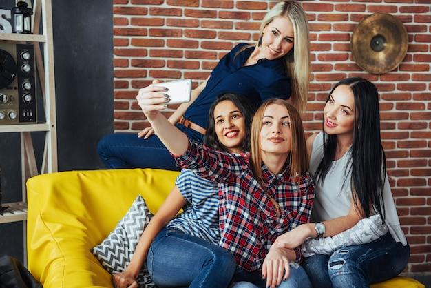 Schöne junge frau vier, die selfie in einem café, mädchen der besten freunde zusammen haben spaß, emotionale lebensstilleute aufwerfend tut Premium Fotos