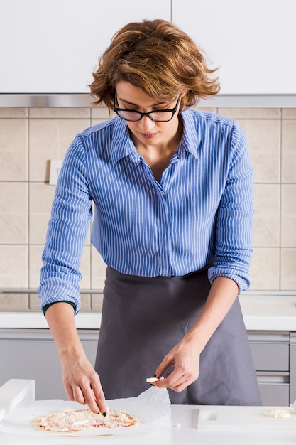Schöne junge frau, welche die pizza in der küche zubereitet Kostenlose Fotos