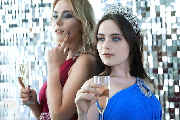 Schöne junge frauen, die mit gläsern wein auf der festlichen party posieren, die der weihnachts- oder neujahrsfeier gewidmet ist Premium Fotos