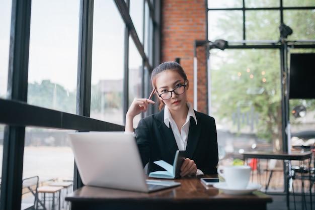 Schöne junge geschäftsfrau, die am tisch sitzt und kenntnisse nimmt. im cafe Premium Fotos