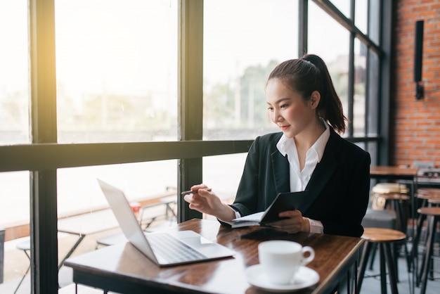 Schöne junge geschäftsfrau, die am tisch sitzt und kenntnisse nimmt Premium Fotos