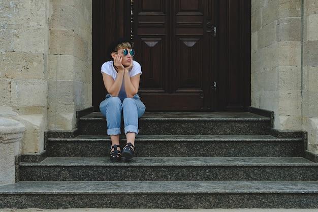 Schöne junge hippie-frau, die das sitzen auf treppe aufwirft Kostenlose Fotos