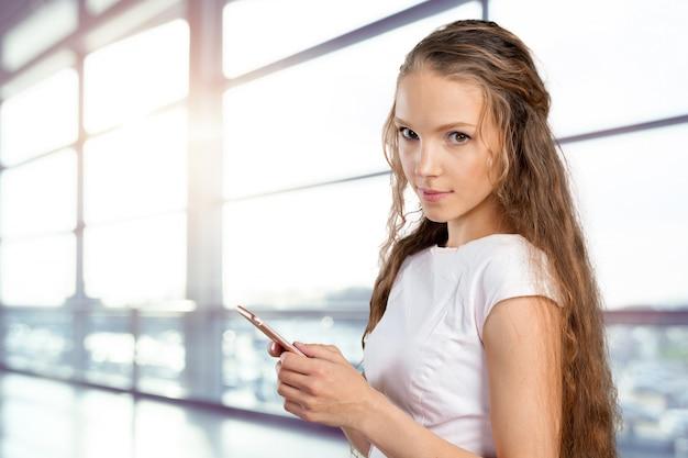 Schöne junge kaukasische geschäftsfrau mit intelligentem telefon Premium Fotos