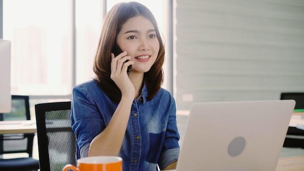 Schöne junge lächelnde asiatische frau, die an laptop beim genießen der anwendung des smartphone im büro arbeitet. Kostenlose Fotos