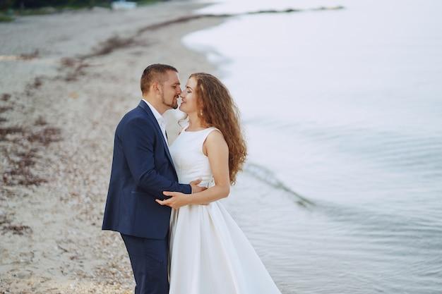 Schöne junge langhaarige braut im weißen kleid mit ihrem jungen ehemann auf dem strand Kostenlose Fotos