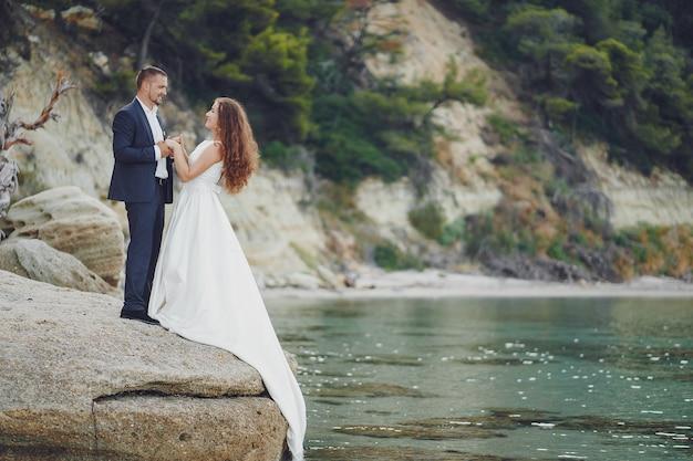 Schöne junge langhaarige braut im weißen kleid mit ihrem jungen ehemann nahe fluss Kostenlose Fotos