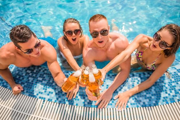 Schöne junge leute, die bier lächeln und trinken. Premium Fotos