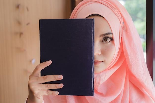 Schöne junge moslemische frau, die ein buch hält, um vor glaswandbüro gegenüberzustellen. Premium Fotos