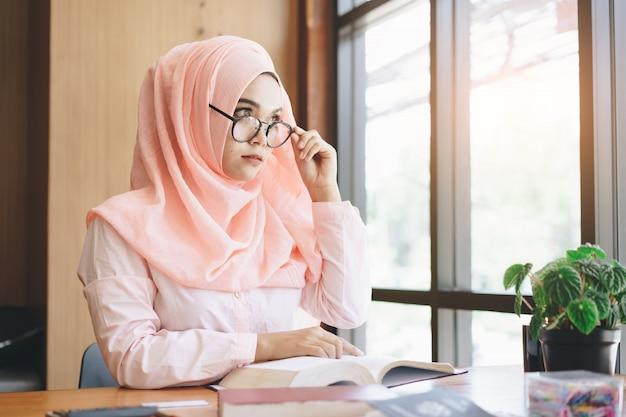 Schöne junge moslemische frau, die ein buch liest und draußen fenster betrachtet. Premium Fotos